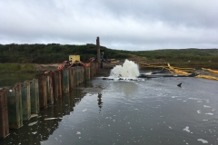 Initial dewatering of the work area behind sheet pile dam, July 2019